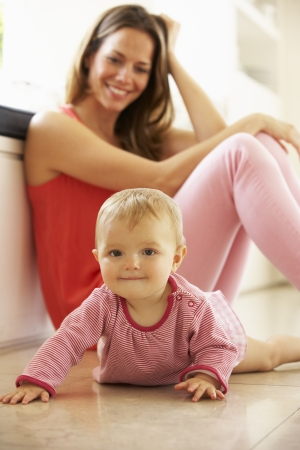 sitting on floor: Mother Sitting With Baby Daughter At Home