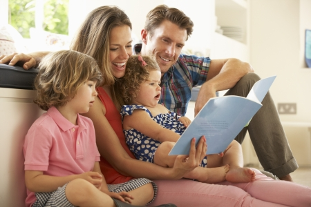 four people: Parents Sitting With Children Reading Story Indoors