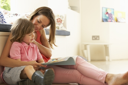 reading: Mother Sitting With Son Reading Story Indoors Stock Photo