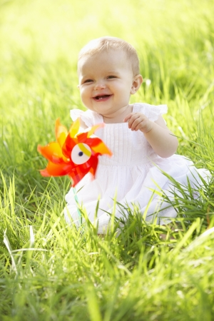 Baby Girl In Summer Dress Sitting In Field Holding Windmill photo