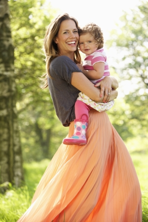 Mother Carrying Young Daughter Through Summer Field Stock Photo - 18709946