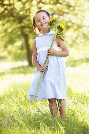 Young Girl Walking Through Summer Field Holding Sunflower photo