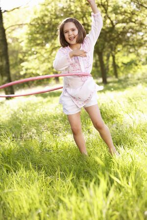 Young Girl Walking Playing With Hula Hoop In Summer Field photo