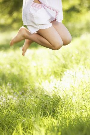pied fille: Gros plan de la jeune fille sauter dans le domaine de l'été Banque d'images