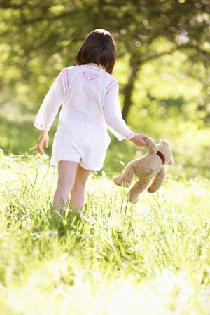 ositos bear: Chica joven que recorre a través de campo de verano que lleva del oso de peluche