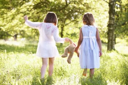 niños caminando: Dos chicas jóvenes caminando a través del campo de verano que lleva del oso de peluche