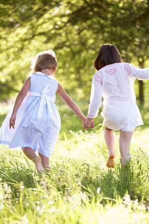 rear view girl: Two Young Girls Walking Through Summer Field Together
