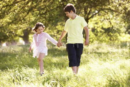 5 10 years old: Boy And Girl Walking Through Summer Field Together