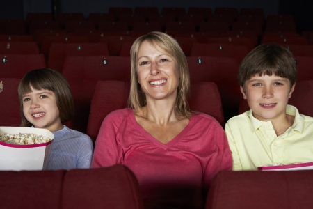 three year old: Mother Watching Film In Cinema With Two Children