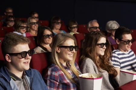 eating popcorn: Group Of Teenage Friends Watching 3D Film In Cinema Stock Photo
