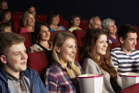 teenagers laughing: Group Of Teenage Friends Watching Film In Cinema Stock Photo