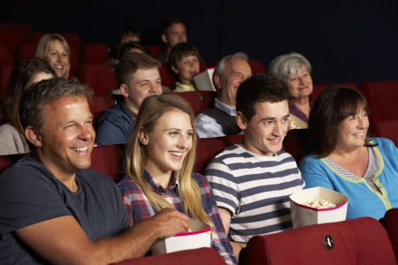 family movies: Teenage Family Watching Film In Cinema Stock Photo