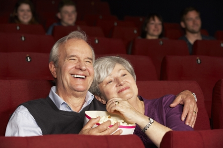 Senior Couple Watching Film In Cinema photo