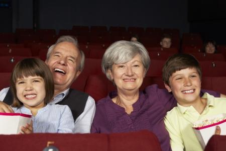 cinta pelicula: Los abuelos viendo pel�culas en el cine con los nietos Foto de archivo