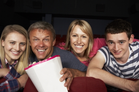 Teenage Family Watching Film In Cinema photo