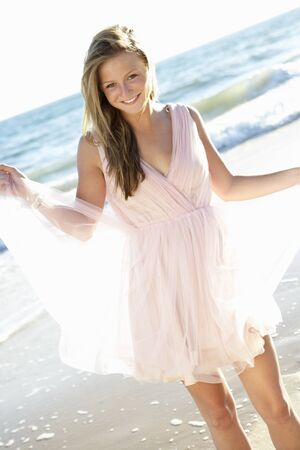 Attractive Teenage Girl Wearing Dress On Beach Holiday photo