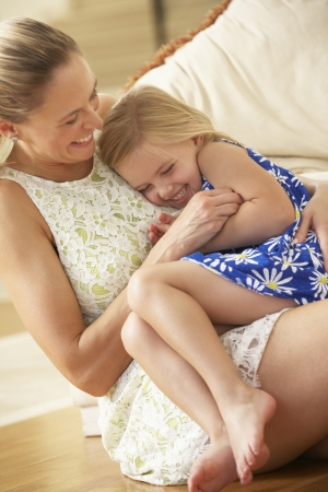 tickling: Mother Relaxing At Home With Daughter Stock Photo