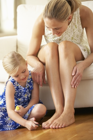 woman sitting floor: Daughter Painting Mothers Toenails At Home