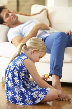 Daughter Painting Sleeping Father's Toenails At Home Stock Photo - 18722452