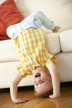 headstand: Young Boy Relaxing On Sofa At Home Stock Photo