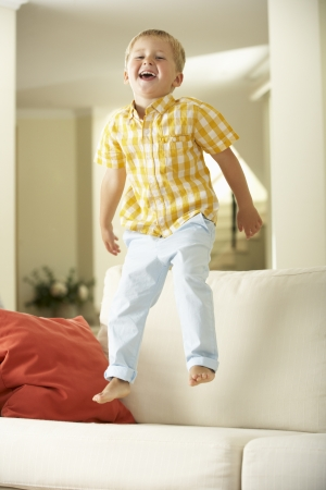 mischievious: Young Boy Jumping On Sofa At Home