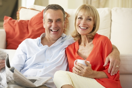 seniors: Senior Couple Relaxing On Sofa At Home Reading Newspaper