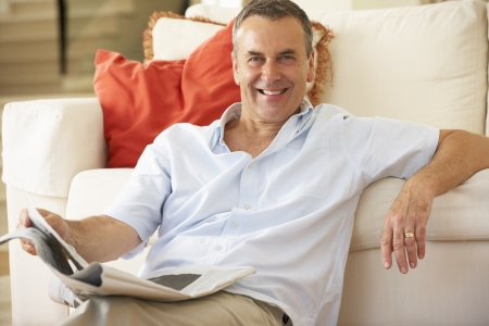 Senior Man Relaxing On Sofa At Home Reading Newspaper photo