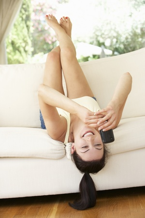 Woman Lying Upside Down On Sofa Sending Text Message photo