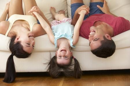 relajado: Family Lying Upside-down En El Sof� Con La Hija Foto de archivo