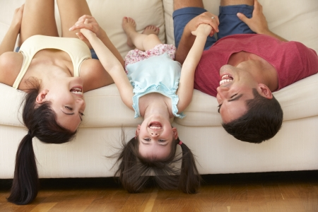 having fun: Family Lying Upside Down On Sofa With Daughter