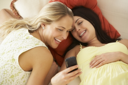 Two female Friends On Sofa Reading Text Message photo
