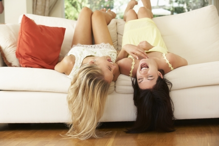 Two Female Friends Lying Upside Down On Sofa photo