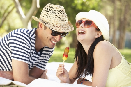 ice cream woman: Couple Relaxing Together In Garden Eating Ice Lolly Stock Photo