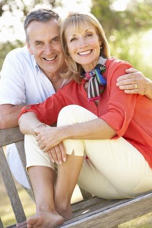 Senior Couple Sitting Outdoors On Bench photo