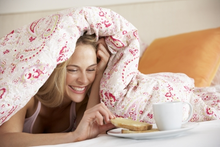 tea hot drink: Pretty Woman Snuggled Under Duvet Eating Breakfast