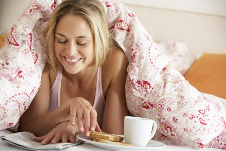 Pretty Woman Snuggled Under Duvet Eating Breakfast And Reading Newspaper photo