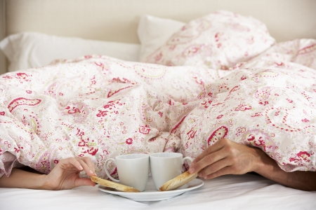 Couple's Hands Reaching From Under Duvet For Breakfast photo