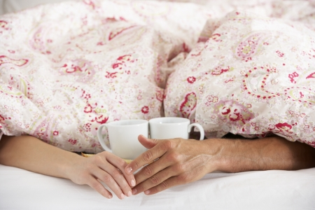 Romantic Couple Holding Hands Under Duvet In Bed photo