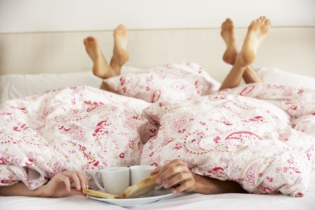 cosy: Couples Hands Reaching From Under Duvet For Breakfast Stock Photo