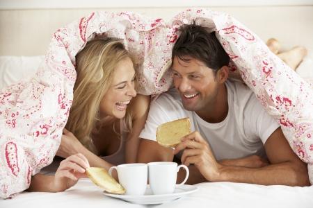 pareja en la cama: Pareja acurrucó bajo Duvet desayunando