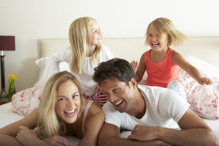 Family Relaxing Together In Bed photo