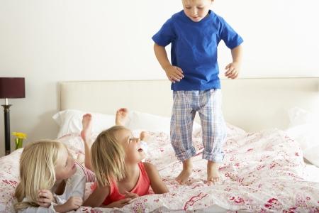 pajamas: Los ni�os Bouncing En La Cama Foto de archivo