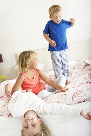 Children Bouncing On Bed photo
