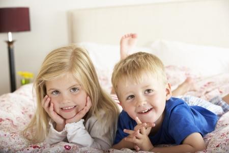 hermanos jugando: Dos niños relax en la cama Foto de archivo