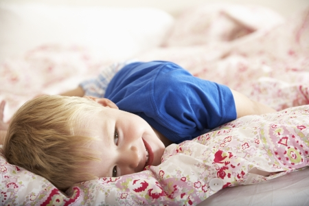 bedding indoors: Young Boy Relaxing On Bed