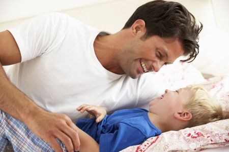 Father And Son Relaxing Together In Bed photo