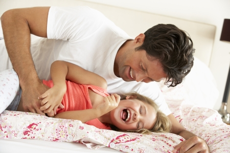 tickling: Father And Daughter Relaxing Together In Bed