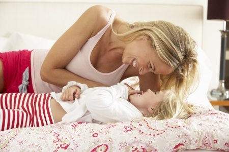 tickling: Mother And Daughter Relaxing Together In Bed Stock Photo