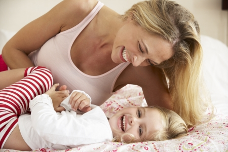 Mother And Daughter Relaxing Together In Bed photo