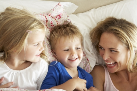 tickling: Mother And Children Relaxing Together In Bed Stock Photo